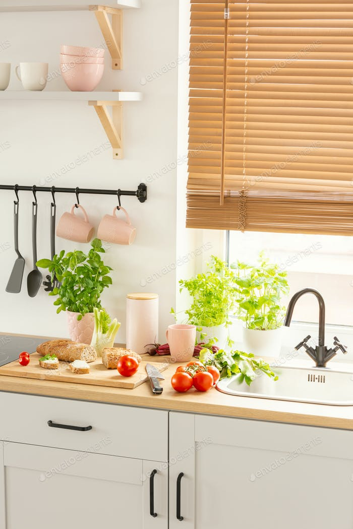 Countertop with bread on wooden board, fresh tomatoes and green