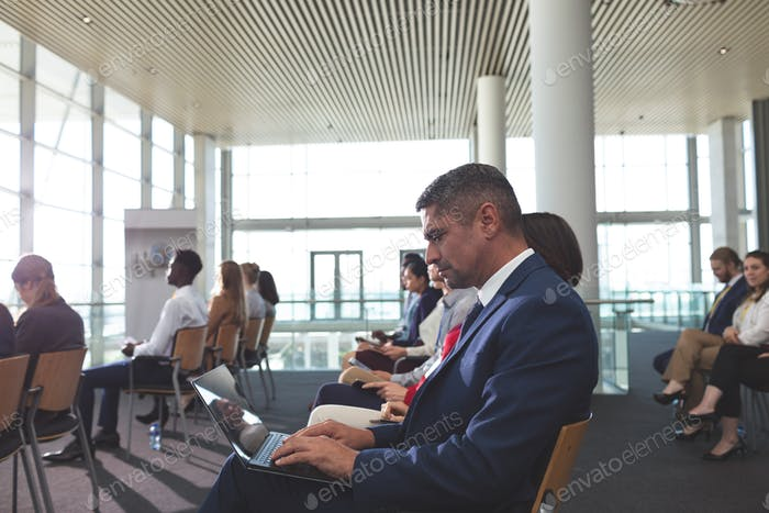 Side view of mixed race businessman using laptop during business seminar in modern office building