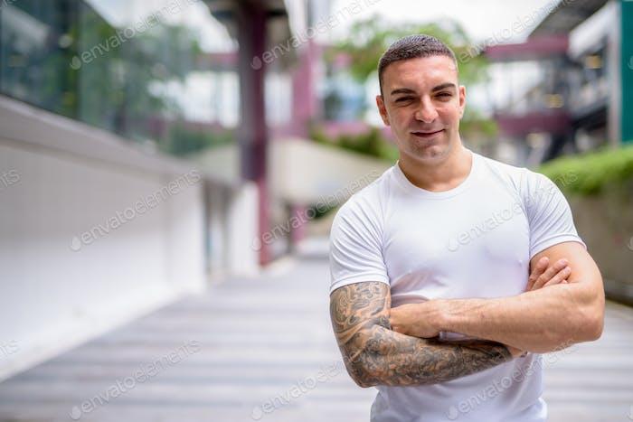 Счастливый красивый мужчина с татуировками улыбается в городе