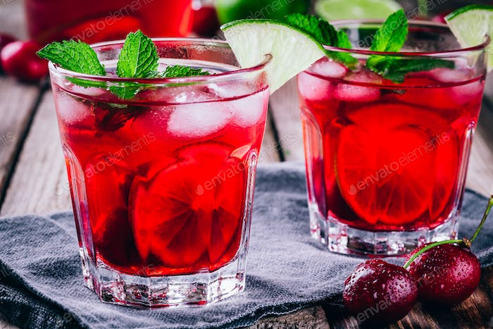 ice refreshing cherry lemonade in glass with ice cubes, lime and mint