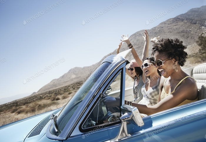 Three young people in a pale blue convertible car, driving on the open road across a flat dry plain,