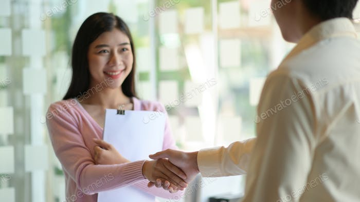Young women and men shakehand to congratulate and smile happily in the modern office.