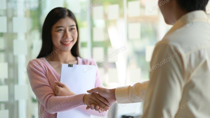 Las mujeres y los hombres jóvenes Shakehand para felicitar y sonreír felizmente en la oficina moderna.