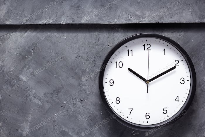wall clock at grey concrete background