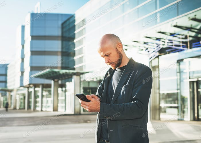 Handsome bald bearded man businessman in suit using mobile phone