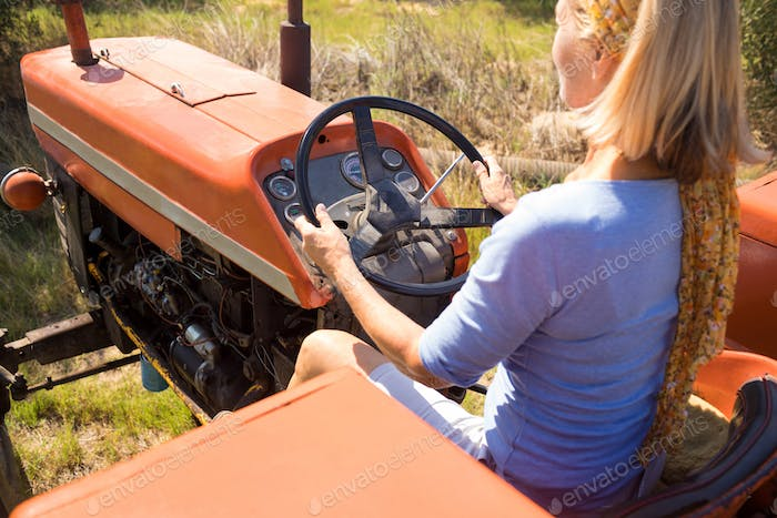 Rear view of woman driving tractor in olive farm