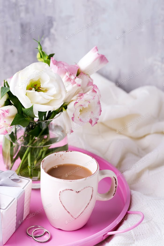 Having a cup of coffee with chocolate, flowers eustoma and gift box on tray on blanket in bed