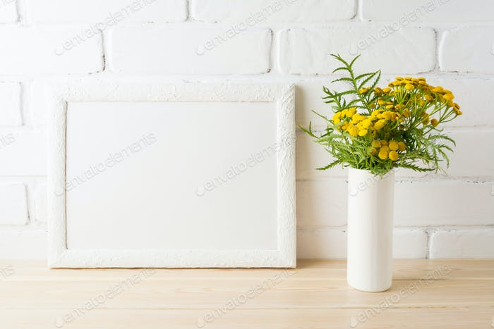 White landscape frame mockup with yellow flowers near painted br