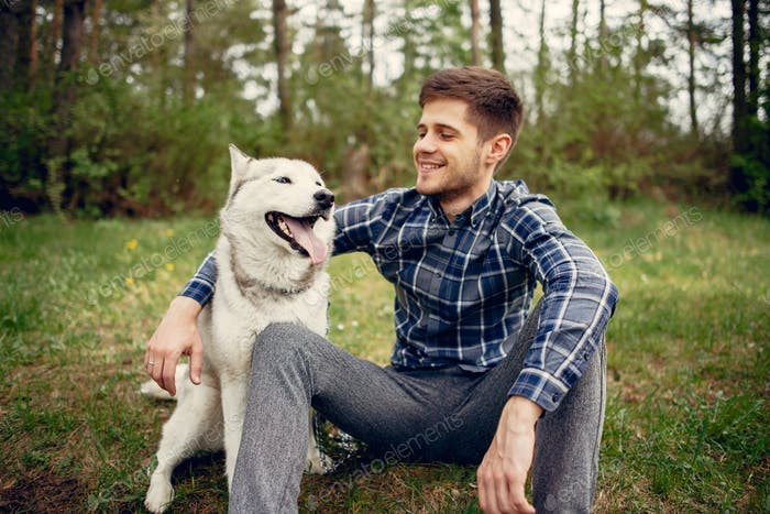 Handsome guy in a summer park with a dog