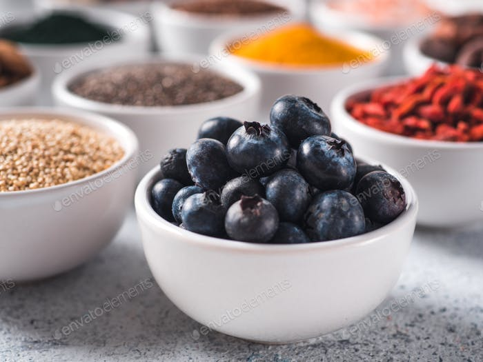Blueberries in small white bowl and other superfoods