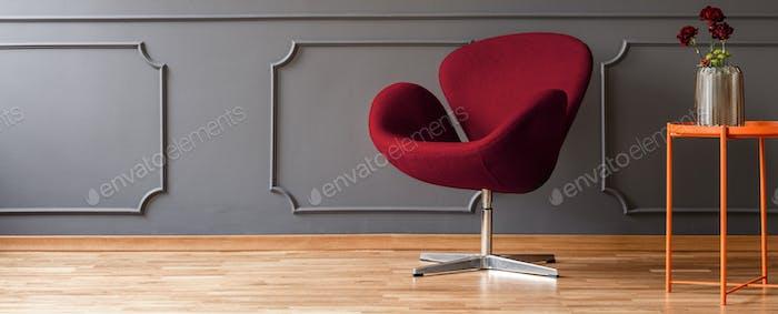 Flowers on an orange side table, a fancy, burgundy red armchair