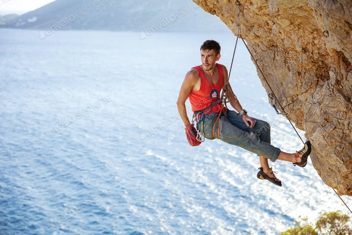 Male rock climber resting while hanging on rope