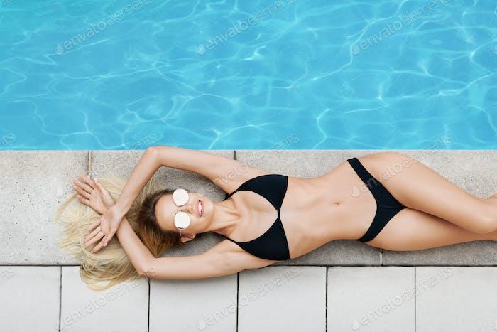 Draufsicht der sexy Millennial Frau liegt in der Nähe von Pool mit klarem blauem Wasser, Leerraum