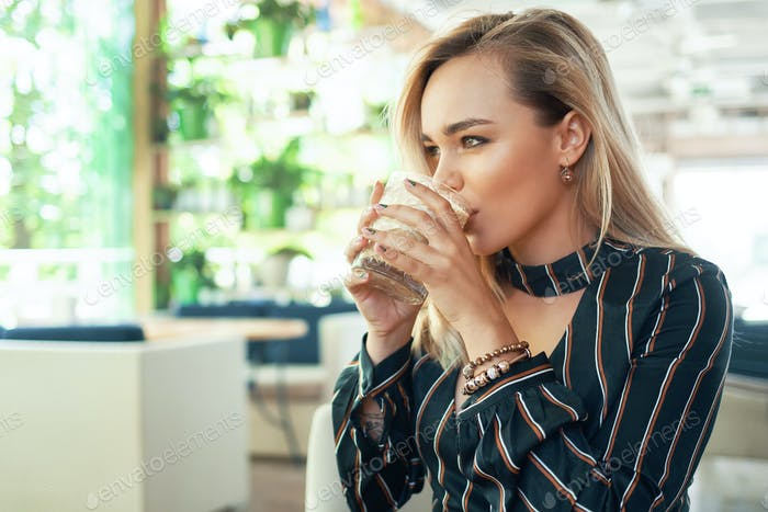 Modern woman drinking a cocktail
