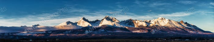 Panoramic shot of winter mountain landscape during sunset. High