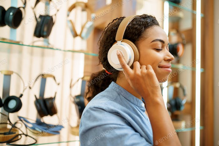 Woman trying on headphones in acoustics store