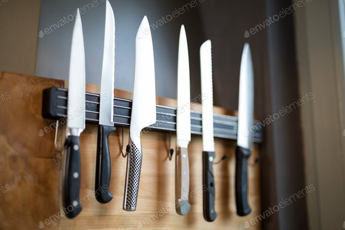 Set of kitchen knives hanging on the wall