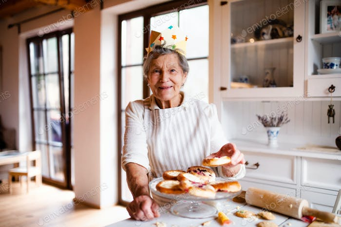 Elderly woman making cakes in a kitchen at home. Copy space.
