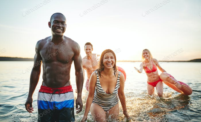 Laughing young friends wearing swimsuits splashing together in a lake
