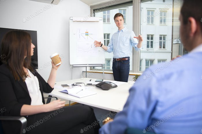 Businessman Gesturing While Giving Presentation To Colleagues