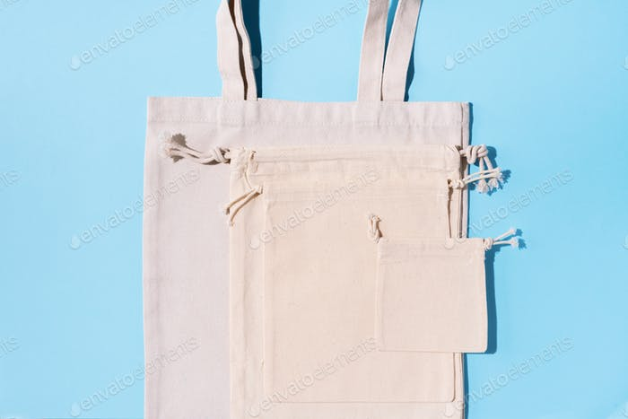 Canvas tote bag canvas and linen fabric bags with drawstring on blue background with copy space. Top