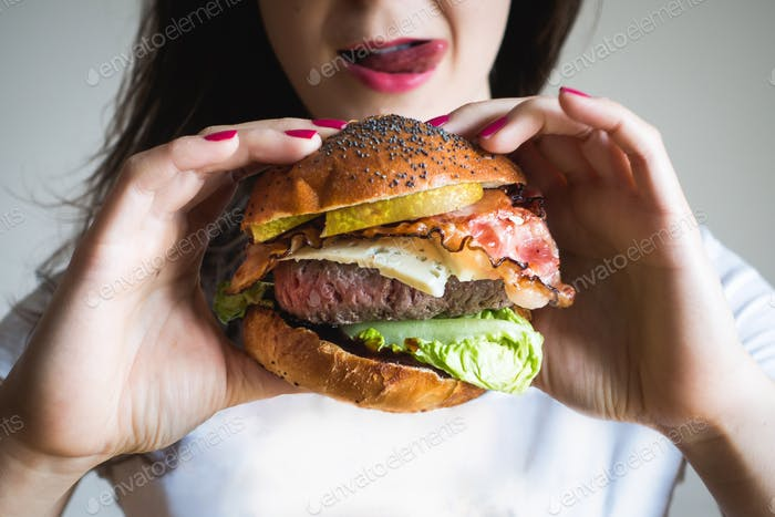 Young lady holding a huge beef burger looking sexy