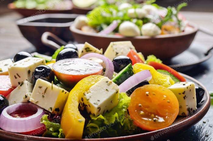 Mediterranean diet dish greek salad on slate tray with sauce as