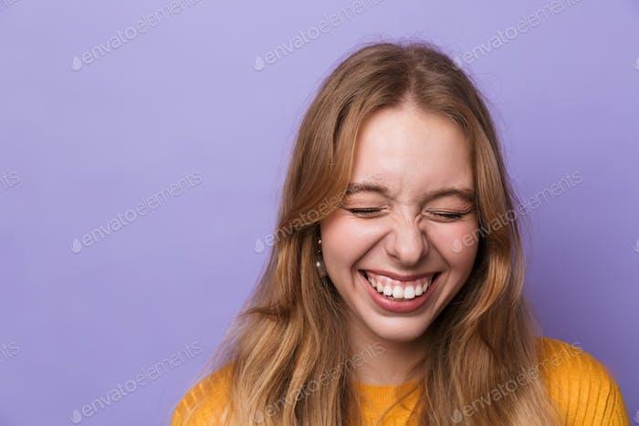 Foto der fröhlichen jungen Frau, die mit geschlossenen Augen lachen