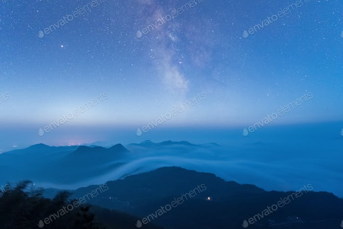 starry sky at the mountain top  and clouds fog in early hours of the morning