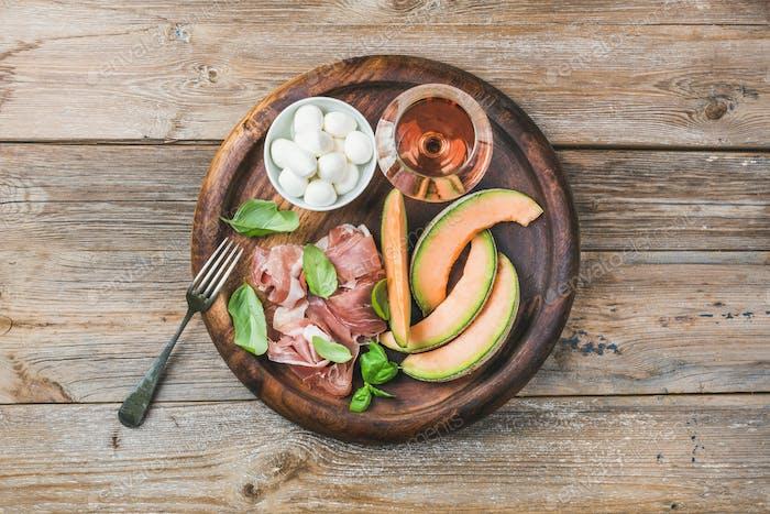 Prosciutto, cantaloupe melon, green basil, mozzarella and glass of wine