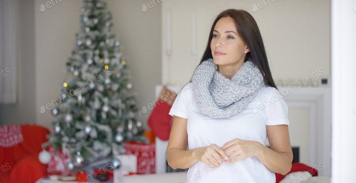Freundliche junge Frau feiert Weihnachten zu Hause