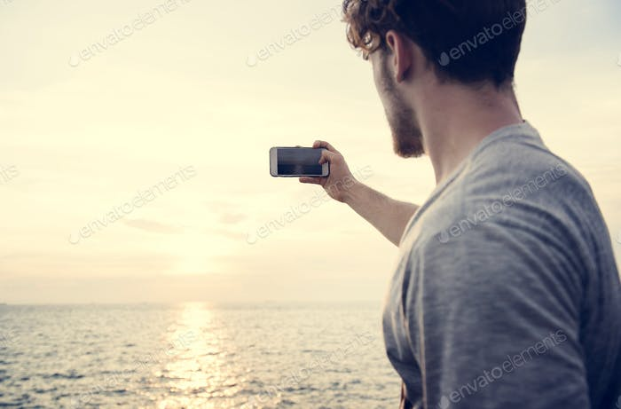 Caucasian man taking a photo of the sunset