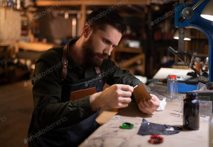 Craftsman applying glue on leather