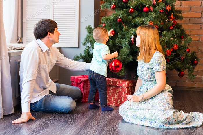 Happy Family Decorating Christmas Tree together. Father, Mother And Son. Cute Child. Kid