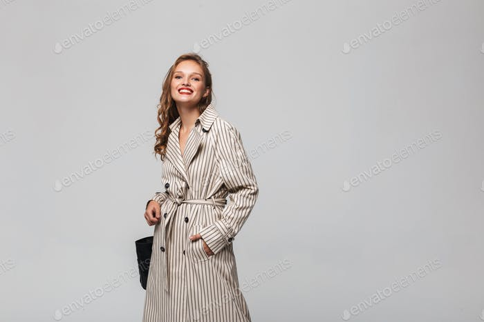 Young pretty cheerful woman with wavy hair in striped coat happily looking in camera