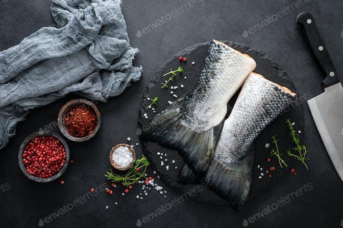 Rohe Lachsfischschwänze mit Zutaten zum Kochen auf schwarzem Hintergrund, Draufsicht