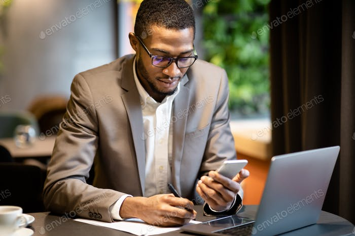 Black business guy taking notes in notebook holding phone