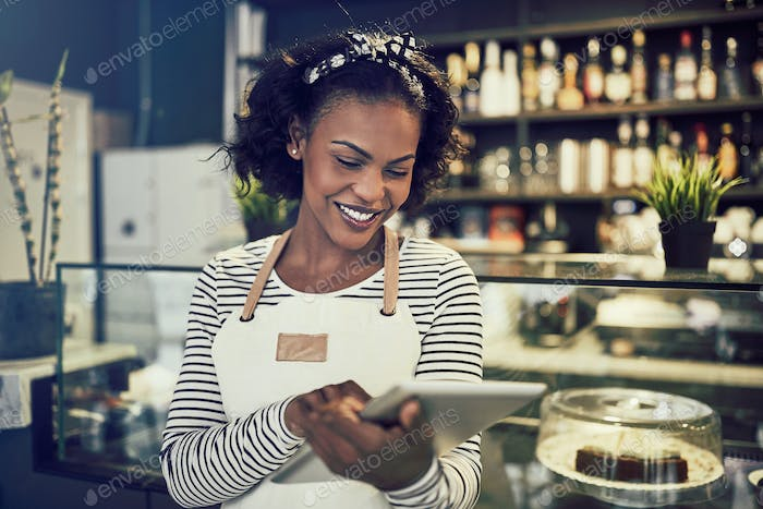 Young African entrepreneur standing in her cafe using a tablet