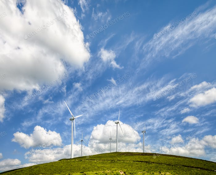Wind turbines on a hill under a blue sky