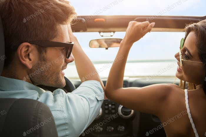 Beautiful young couple sitting on the front passenger seats