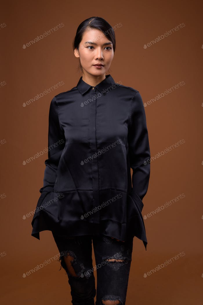 Studio shot of beautiful Asian businesswoman with hair tied