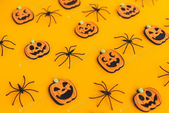 Happy Halloween. Pumpkins jack o lantern and spiders on orange background. Pattern