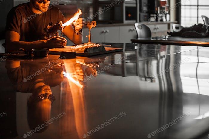 Glasbläserer junger Mann, der auf einer Fackel Flamme mit Glasröhren arbeitet