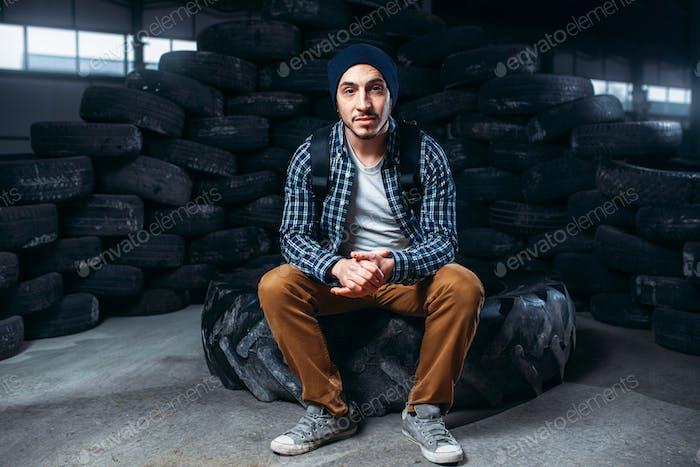 Stalker, alone traveler against mountain of tires