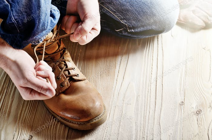 Zimmermann in blauen Jeans binden Schnürsenkel von gelben Arbeitsstiefel auf