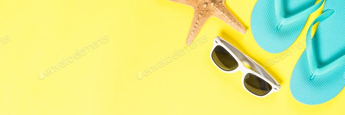 Blue flip flops, sunglasses and starfish on yellow top view