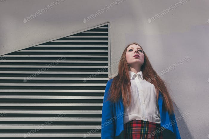 Beautiful redhead girl posing in an urban context