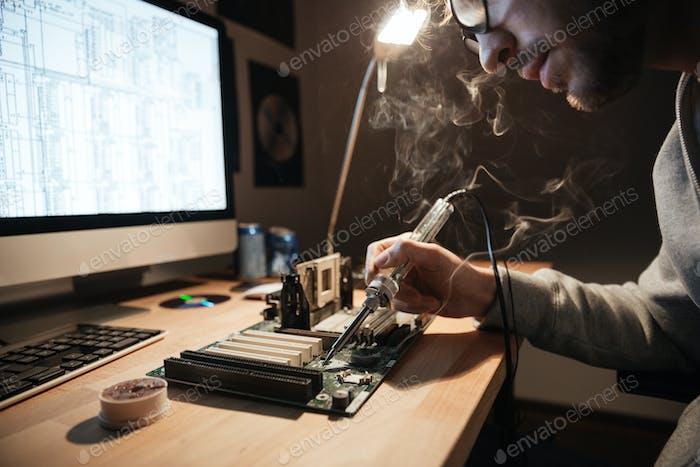 Serious man using scheme soldering iron for repairing motheboard
