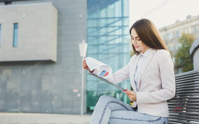 Caucasian businesswoman working with papers outdoors