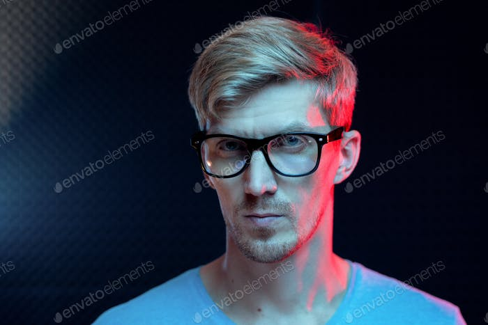 Young serious man with blond hair standing by wall in dark studio in isolation